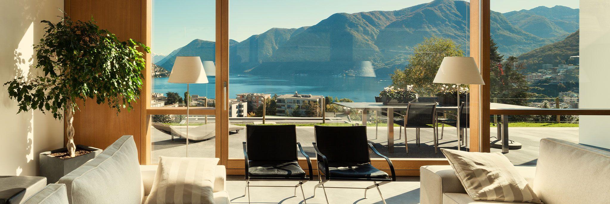 Blick aus Ferienhaus mit Terrasse auf See und Berge