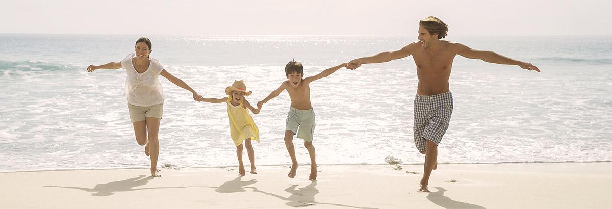 Familie rennt ausgelassen im Urlaub am Strand