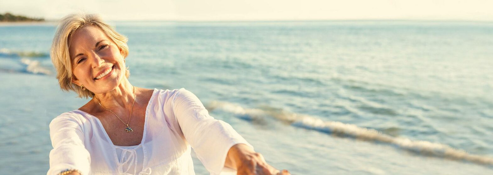 Glückliche Frau im Urlaub am Wasser