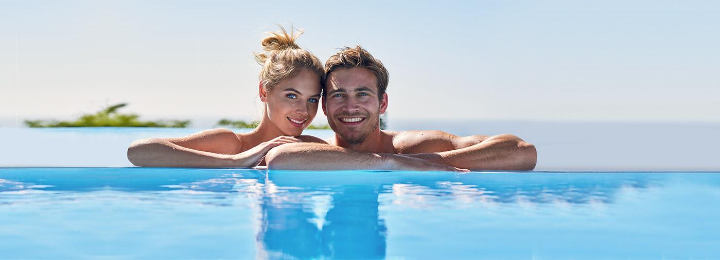 Paar badet im Pool und lächelt in die Kamera